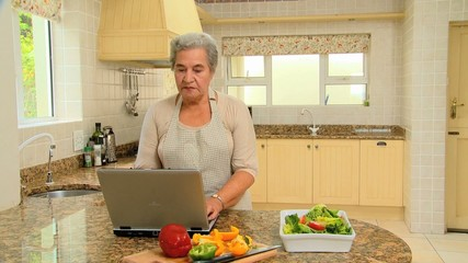 Retired woman looking up a recipe on her laptop