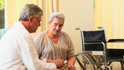 Doctor explaining her medication to a mature patient