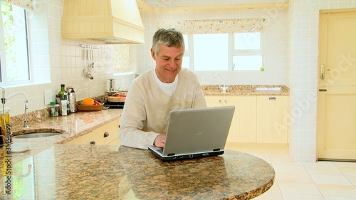 Mature man using a laptop in the kitchen