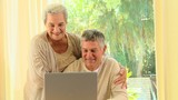 Mature couple smiling about something on a laptop