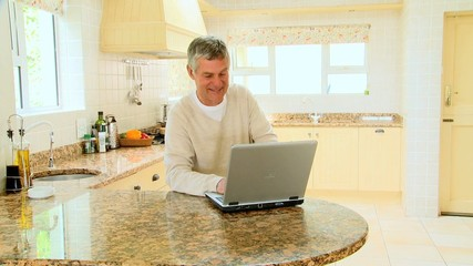 Man using a laptop in the kitchen