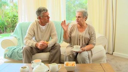 Mature couple sitting drinking tea and chatting