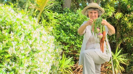 Mature woman showing her garden produce