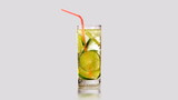 Rotating glass of lemonade with lime green. Isolated.