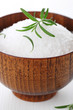 Sea salt with fresh rosemary in wooden bowl closeup