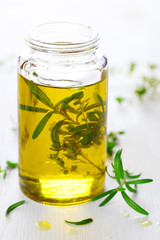 Scented oil with rosemary and fresh herbs on white wooden backgr