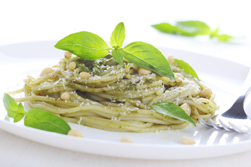 Pasta with pesto sauce, fresh basil and pine nuts on white plate