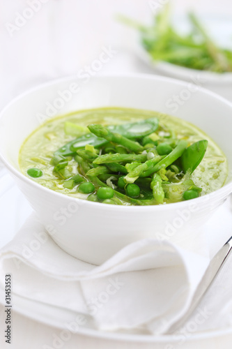 Cream soup with asparagus, peas and leeks in white plate