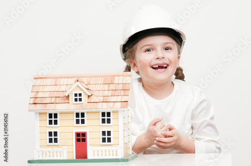 Little girl with house model