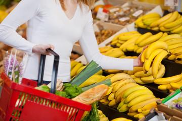 frau im supermarkt kauft bananen