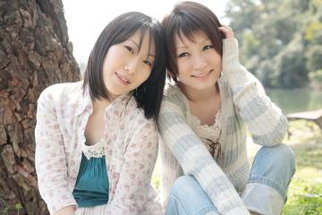 木の前に座る女性二人