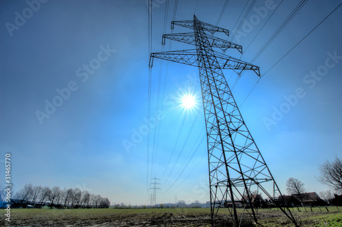 Electricity transmission pylon with sun on the background