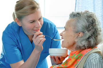 senior woman 90 years old being fed by a nurse