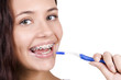 happy girl with braces brushing her teeth