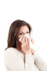 Junge Frau schneuzt in Taschentuch