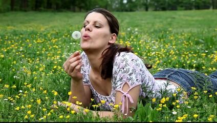 Ragazza in un campo che soffia su un fiore