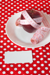 Red apple and measuring tape on a white plate