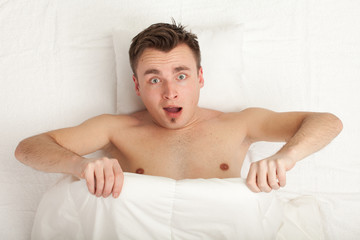 surprised young handsome man in white bedding, series