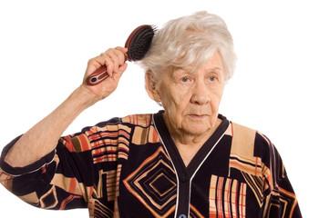 The elderly woman brushes hair