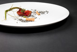 A plate with  cigarette and strawberry