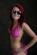 Pretty young woman in pink bikini and sunglasses