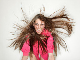 Screaming furious aggressive brunette lady with flying long hair