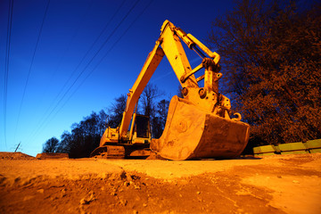 Big crawler tractor with big bucket on yellow sands at night