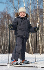 Young boy stands on cross-country skis inside winter forest