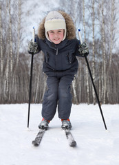 Young boy stands on cross-country skis and leans on poles inside