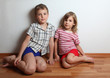 Little boy and thoughtful girl in home clothes sitting