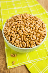 Sweet popped wheat grains in bowl on wooden background