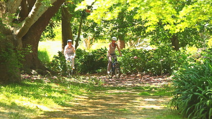 Athletic young couple cycling in a wood