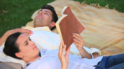 Couple relaxing reading a book  outdoors