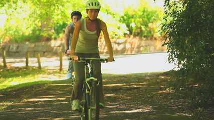 Sporting couple cycling on a path