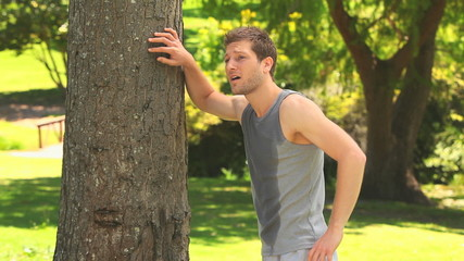 Man resting against a tree after jogging