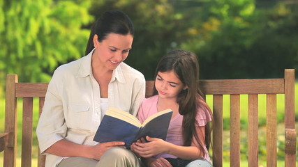 Mother with her daughter reading a book