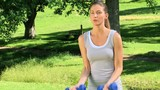 Good looking woman in a park with dumbbells