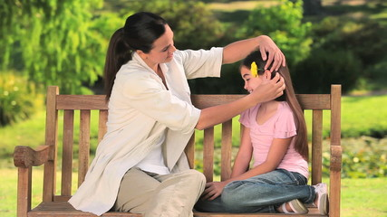 Mother putting a flower on her daughter hair
