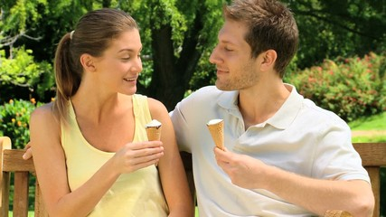 Friends enjoying ice cream on a bench
