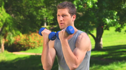 Handsome man using dumbbells in a park