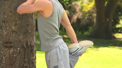 Man in sportswear stretching against a tree