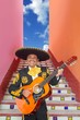 Charro Mariachi playing guitar in Mexico stairway