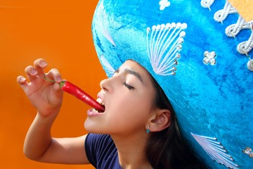 Mexican girl eating red hot chili pepper