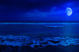 Fototapety Night scene in a deserted beach with a crescent moon