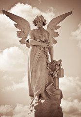Young female angel in sepia tones against a dramatic sky