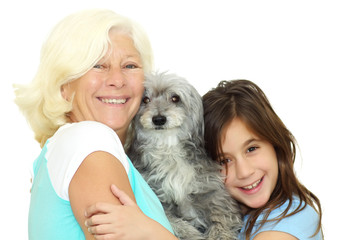 Grandmother and girl hugging the family dog a white background