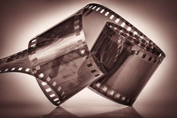 35 mm film on a dramatically illuminated dark sepia background