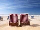 red beach chairs on a deserted sunny beach