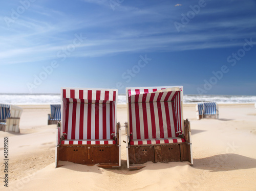 Leinwandbild Motiv red beach chairs on a deserted sunny beach