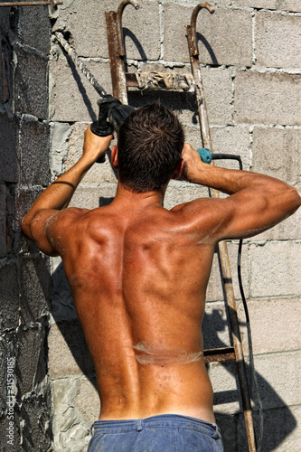 Muscle sexy naked dirty young worker with drill